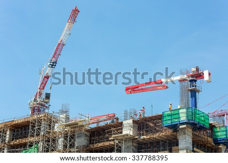 building and cranes under construction against blue sky - stock photo