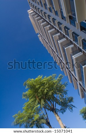 Building and tree under blue sky - stock photo