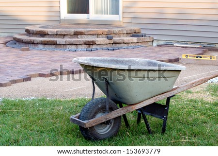Building Brick Patio with Barrel and level, newly built steps with slopes at background,a clean patio job completion almost done - stock photo