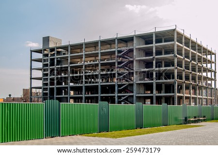 Building construction copyspace on the sky toned colorized image. Construction site. Modern building under construction and green metal fence. - stock photo