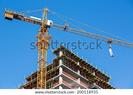 Building construction site with tower crane against blue sky - stock photo