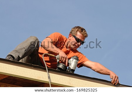 Building contractor putting the asphalt roofing on a large commercial apartment building development - stock photo