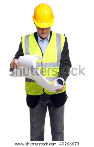 Building contractor wearing safety clothing as he unfolds some blueprints, isolated on a white background. - stock photo