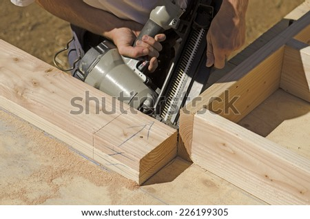 Building contractor worker laying out the base plate of a interior bearing wall for the first floor on a new home construction project - stock photo