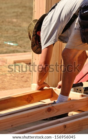 Building contractor worker using a air nail gun to attach studs to the top and base plate of the wall for the first floor on a new home construction project - stock photo