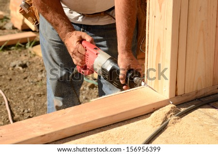 Building contractor worker using a reciprocating saw to cut out the door in the base plate of the wall for the first floor on a new home construction project - stock photo