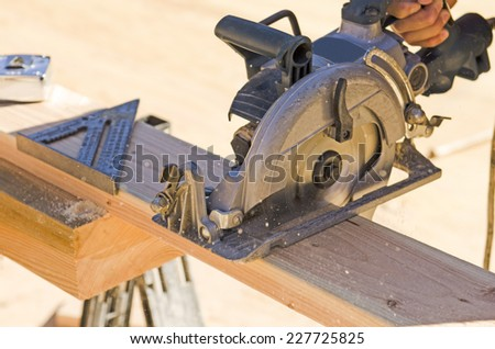 Building contractor worker using hand held worm drive circular saw to cut boards on a new home construction project - stock photo