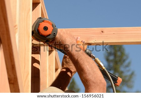 Building contractor worker walking the wall and securing the top plate of the wall for the first floor on a new home construction project - stock photo
