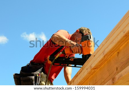Building contractor worker with a air nail gun  nailer working on the corner of the top plate of the first floor walls on a new home constructiion project - stock photo