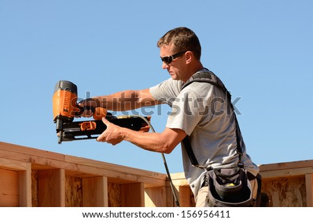 Building contractor worker working on the corner of the top plate of the first floor walls on a new home construction project - stock photo