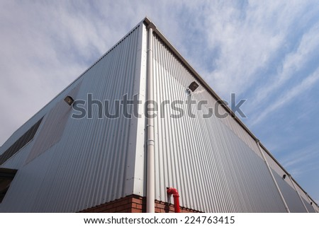 Building Corner Meat Sheeting Corner section of factory warehouse building built with metal  structure with  roofing cover sheeting and brick block walls - stock photo