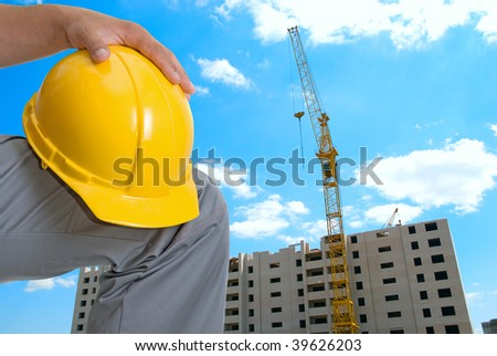 Building crane and builder under construction on blue cloudy sky
