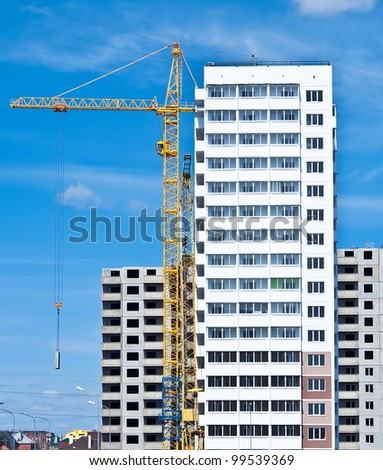 Building crane and building under construction against blue sky - stock photo