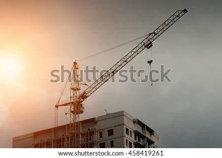Building crane and the roof of a multistory building against the sky, sunset or sunrise