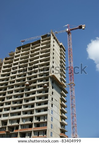 Building crane at the background of a multi-storey building under construction - stock photo