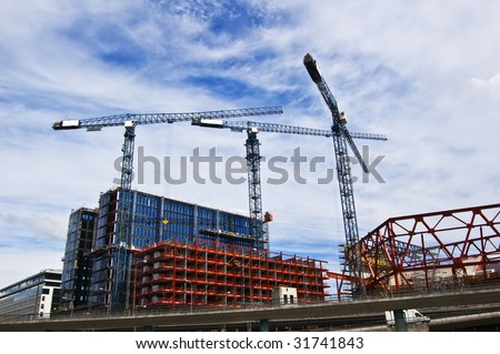 Building cranes in action in Stockholm - stock photo