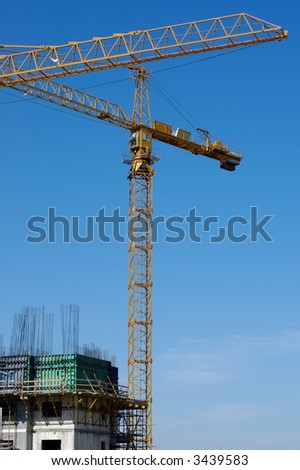 building, cranes on background of blue sky
