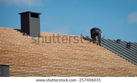 Building crew working on the roof sheeting - stock photo