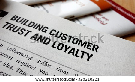 Building customer trust and loyalty word on a book. Business success concept