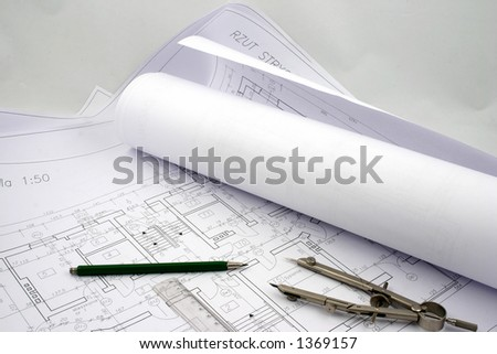 Building designs, some in a rolls of paper put together with pencil, ruler and compasses - stock photo