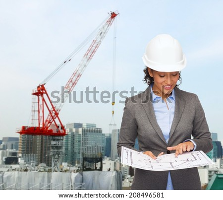 building, developing, construction and architecture concept - smiling businesswoman in white helmet pointing finger to blueprint