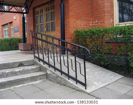 Building entrance with ramp for disabled person wheelchair - stock photo