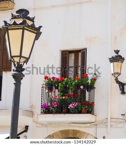 Building facade with beautiful balcony full of flower pots - stock photo