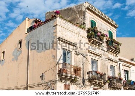 Building facades with windows and wrought iron balconies very spoiled in the historic center of Ortigia, Syracuse, Sicilia, Italy