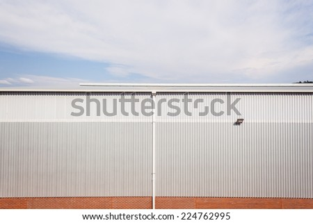 Building Factory Warehouse Section of factory warehouse building built with metal  structure with roofing cover metal sheeting and brick block walls - stock photo