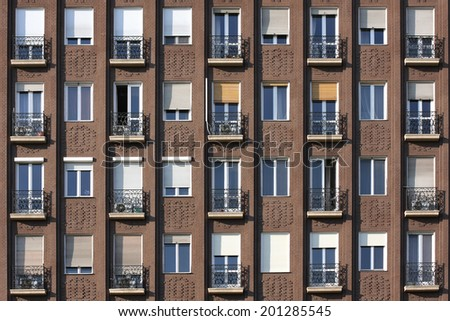 building front wall with repeting pattern of windows and balcony - stock photo