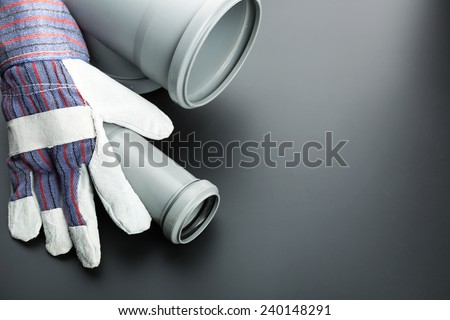 Building glove and soil-pipe on grey - stock photo