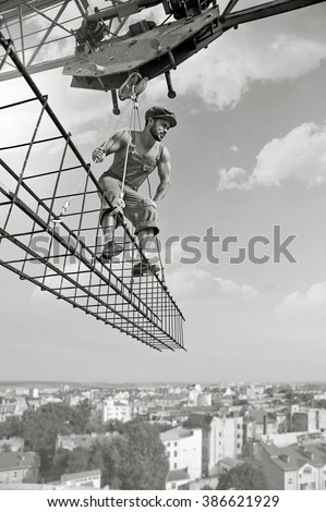 Building his city. Low angle monochrome shot of a builder man looking attentively standing on a crossbar hanging over the skyscraper - stock photo