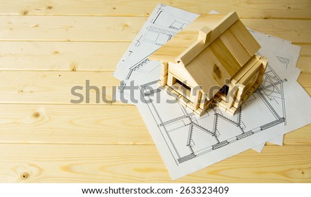 Building house. House construction. Many drawings for building and wooden house on wooden background. - stock photo