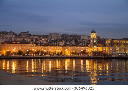 Building in the evening on the Adriatic Coast with reflection on the water, Trieste, Italy. - stock photo