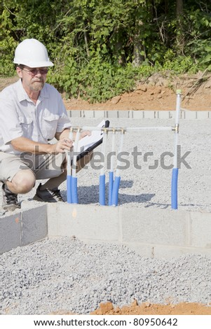 Building inspector checking new electrical & plumbing pipes coming into new residential community - stock photo