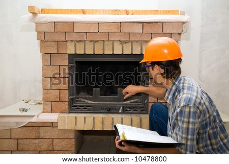 building master examines a new fireplace - stock photo