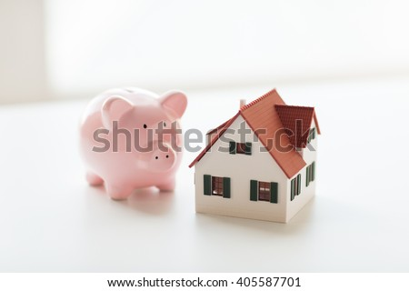 building, mortgage, investment, real estate and property concept - close up of home or house model and piggy bank - stock photo