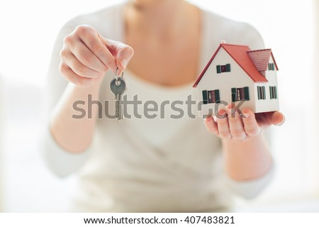 building, mortgage, real estate and property concept - close up of hands holding house model and home keys - stock photo