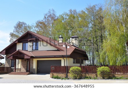 Building New House with Ceramic Tiles Roofing, Garage and Cozy Garden - stock photo