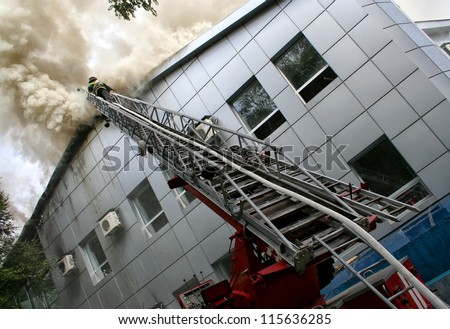 Building on fire. firefighter puts out a fire while on a ladder - stock photo