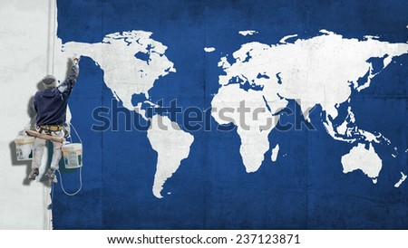 building painter hanging form harness painting  a blue facade with a white world map - stock photo