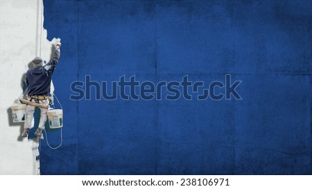 Building Painter hanging from harness painting a wall in blue with lots of copy space for your own, message - stock photo