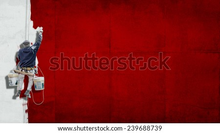 Building Painter hanging from harness painting a wall in red with lots of copy space for your own, message - stock photo