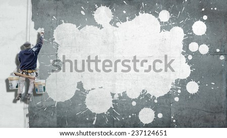 Building Painter hanging from harness painting a wall with splatters ideal for inserting your own message - stock photo