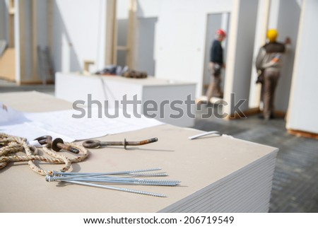 Building plan, eye bolt and screws on plasterboard panels with workers in background - stock photo
