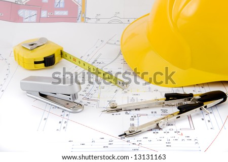 Building plan with safety helmet, pair of compasses and rolling meter