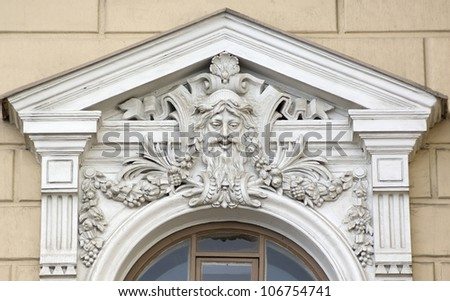 Building relief detail of architectural frieze with human head