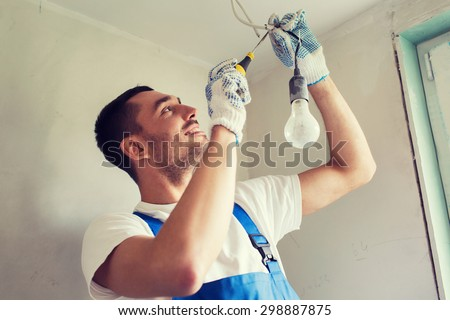 building, renovation, technology, electricity and people concept - builder with screwdriver fixing socket indoors - stock photo