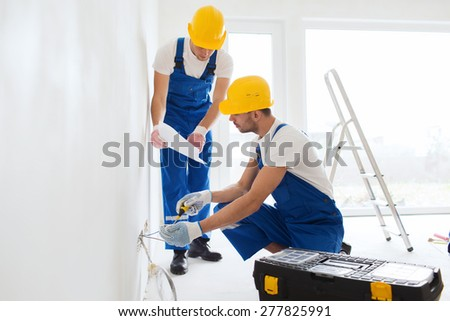 building, renovation, technology, electricity and people concept - two builders with tablet pc computer working with electricity indoors - stock photo