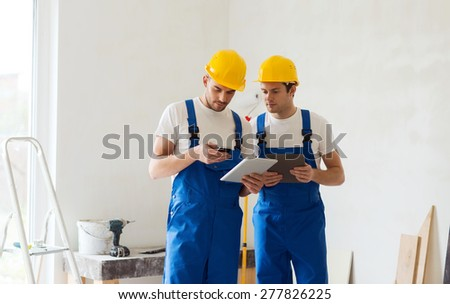 building, renovation, technology, electricity and people concept - two builders with tablet pc computer and smartphone indoors - stock photo
